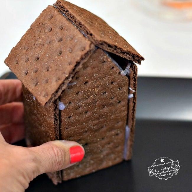 Assembling a graham cracker house with glue