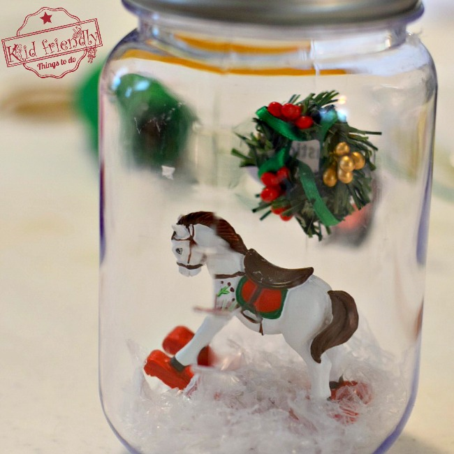 DIY Mason Jar Snow Globes for a Winter or Christmas Craft - OR - Christmas Ornament - Perfect for Christmas parties with kids! So much fun. - www.kidfriendlythingstodo.com