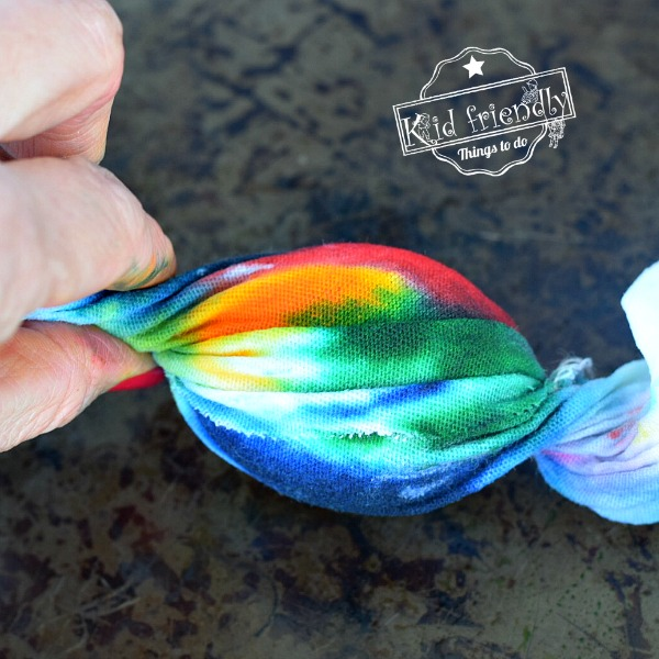 Twisting colorful fabric around the egg to dye it for Easter