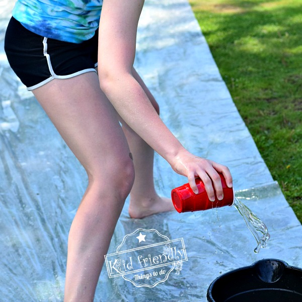 Filling up a bucket with water during a water relay race