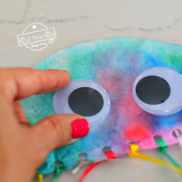 Adding google eyes to Coffee Filter Jelly Fish Ocean Craft