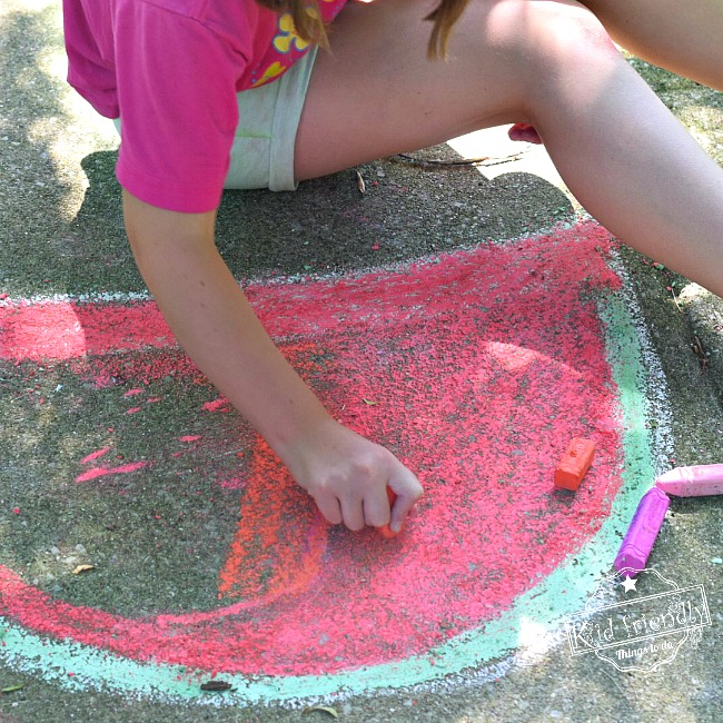 Drawing a watermelon out of chalk for seed spitting contest